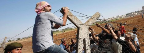 Turkish and Syrian Kurds pull down a part of the Turkish-Syrian border fence, near Suruc in Sanliurfa province