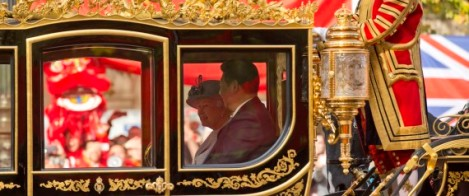Chinese President Xi Jinping, right, sits beside Britain's Queen Elizabeth II, in a horse-drawn carriage passing a large Chinese flag on the route along the Mall to Buckingham Palace in London, Tuesday, Oct. 20, 2015. Chinese President Xi Jinping prepared to address Britain's Parliament and dine with Queen Elizabeth II Tuesday as he began a state visit that is intended to cement close economic ties between the two countries — but risks being overshadowed by concerns over Beijing's growing economic clout in Britain. (AP Photo/Matt Dunham)